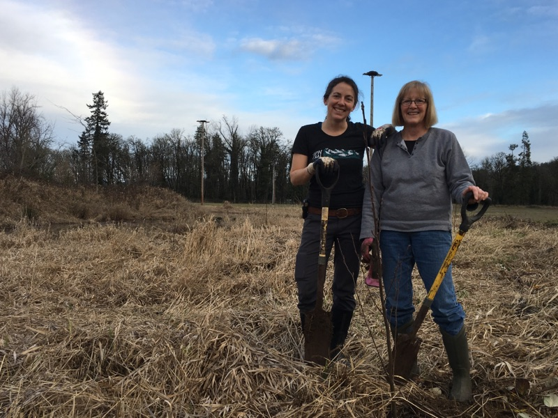 Two white women pose behind a young tree holding shovels and smiling.